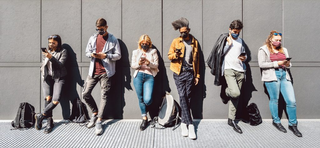 Multiracial people using mobile smart phone with face mask covered